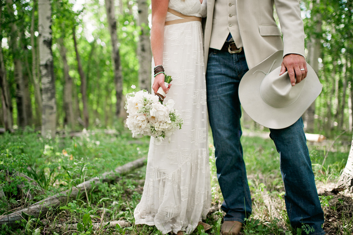 Bride with white bouquet in forest, groom with cowboy hat